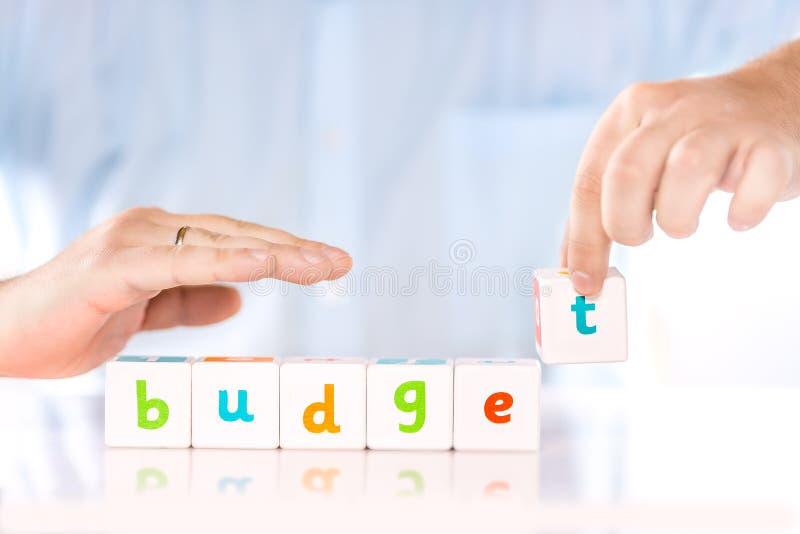 Erklären, Finanz- oder Geschäftskonzept ein Bankkonto habend Männliche Hände sammeln Wort Budget von den Würfeln stockfotos