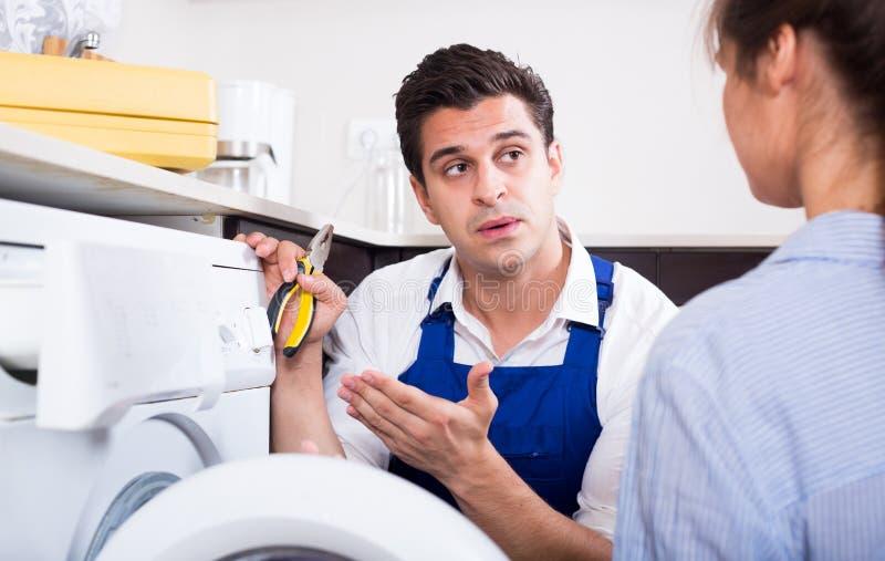 Erklärende Frau des Schlossers, wie man Waschmaschine benutzt lizenzfreies stockbild