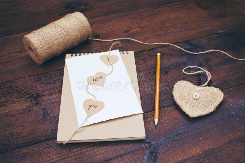 Erklärung der Liebe Valentinsgrußtageshandwerkskartenideen Grußkarte mit Text ICH LIEBE DICH auf Handwerksrecyclingpapiernotizbuc lizenzfreie stockfotografie