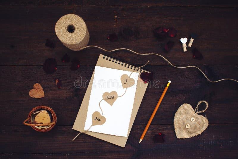 Erklärung der Liebe Valentinsgrußtageshandwerkskartenideen Grußkarte mit Text ICH LIEBE DICH auf Handwerksrecyclingpapiernotizbuc stockfotos