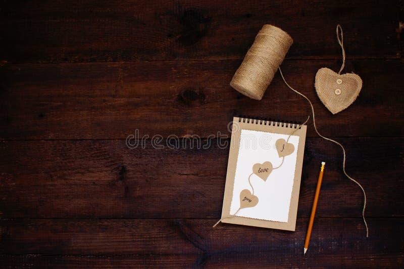 Erklärung der Liebe Valentinsgrußtageskartenideen Grußkarte mit Text ICH LIEBE DICH auf Handwerksrecyclingpapiernotizbuch, Bleist lizenzfreies stockfoto