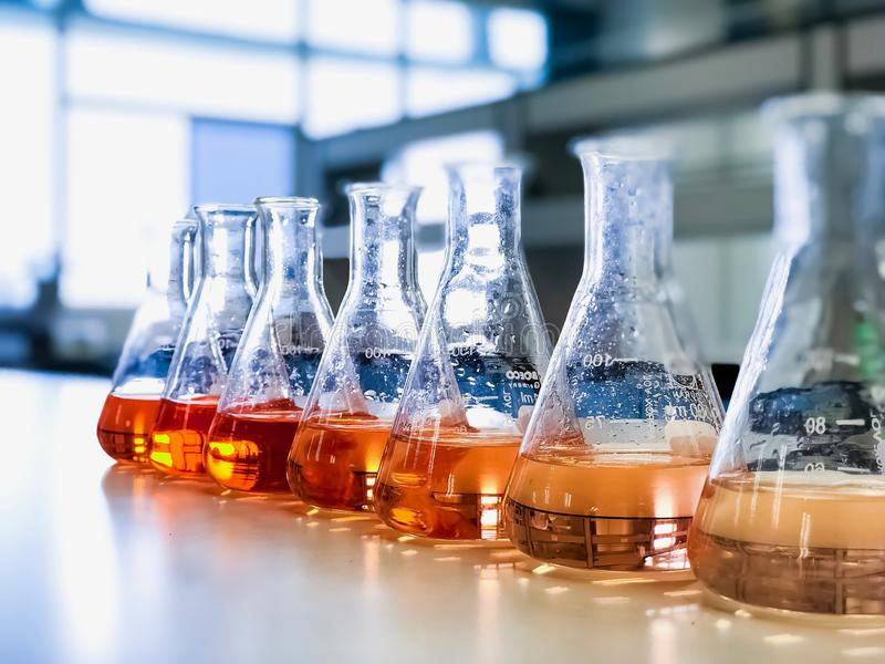 The Erlenmeyer or Conical flask on bench laboratory, with gradient solvent for analysis concentration range of iron show orange. The Erlenmeyer or Conical flask royalty free stock images