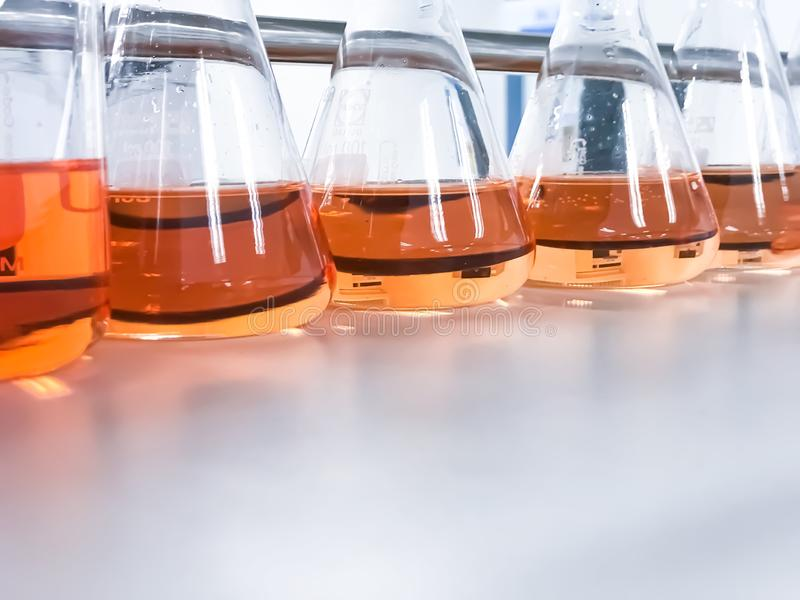 The Erlenmeyer or Conical flask on bench laboratory, with gradient solvent for analysis concentration range of total iron. The Erlenmeyer or Conical flask on royalty free stock image