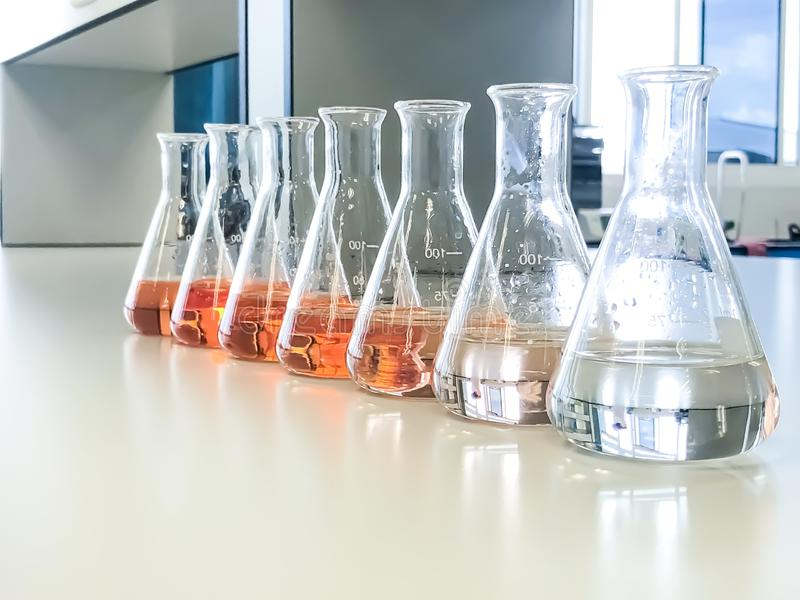 The Erlenmeyer or Conical flask on bench laboratory, with gradient solvent for analysis concentration range of total iron. The Erlenmeyer or Conical flask on stock image