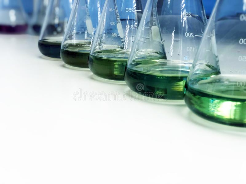 The Erlenmeyer or Conical flask on bench laboratory, with green solvent from forming reaction between boric acid and ammonia. stock photography