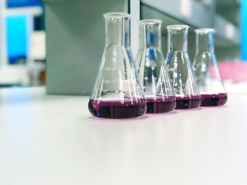 The Erlenmeyer or Conical flask on bench laboratory, with purple solvent forming reaction between boric acid and ammonia solution. The Erlenmeyer or Conical royalty free stock photography