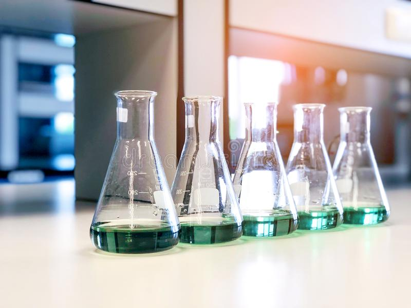 The Erlenmeyer or Conical flasks on bench laboratory, with range of green solvent forming reaction between boric acid and ammonia. The Erlenmeyer or Conical stock photo