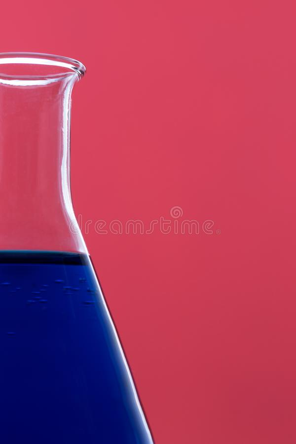Erlenmeyer flask. Close up of erlenmeyer flask over pink background royalty free stock photo