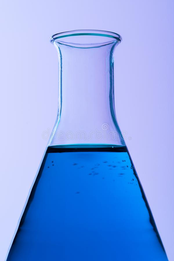 Erlenmeyer flask. Close up of erlenmeyer flask over purple background stock photo
