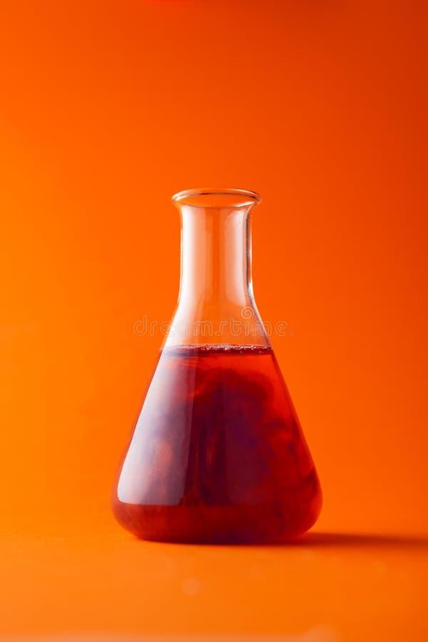 Erlenmeyer flask. Over orange background stock images