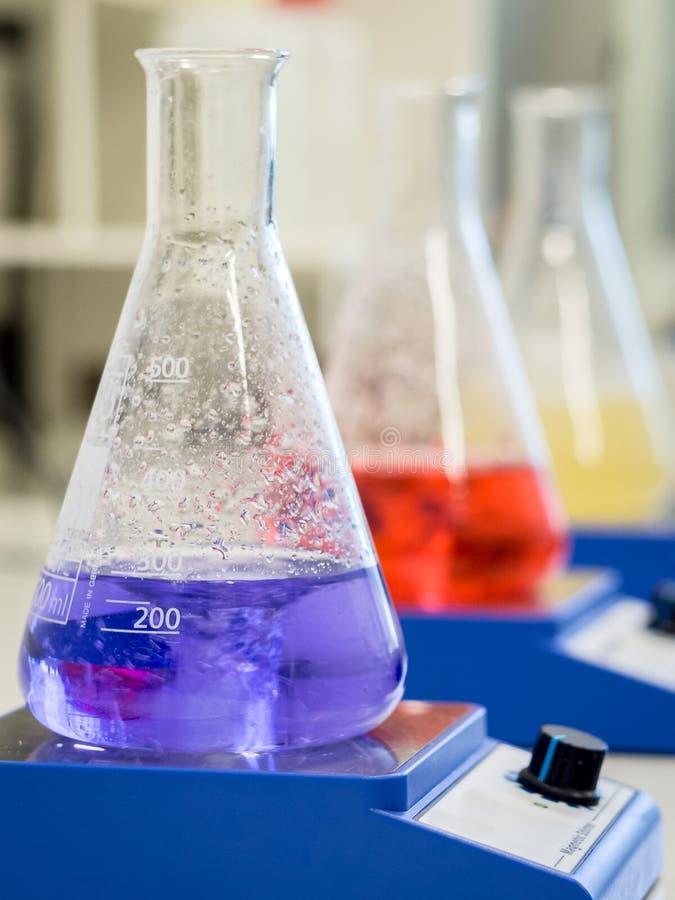 Erlenmeyer flaskor med färgrika lösningar fotografering för bildbyråer
