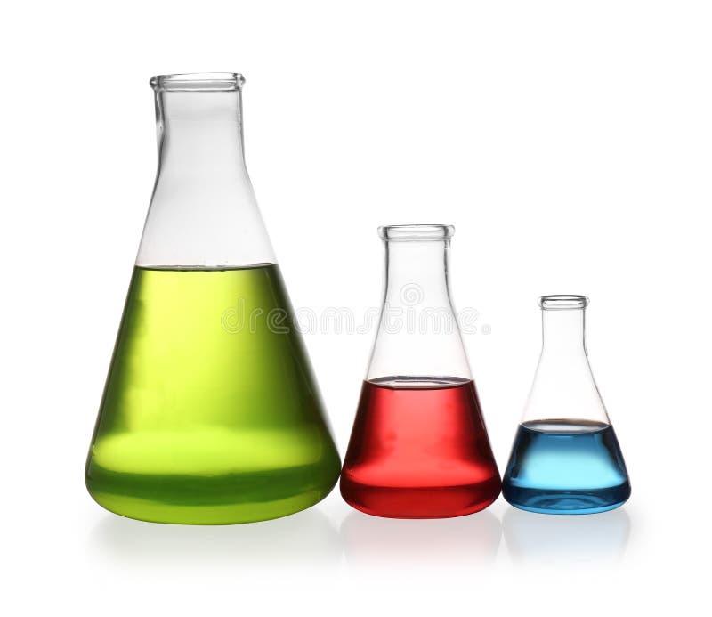 Erlenmeyer flaskor med isolerade färgflytande royaltyfria foton