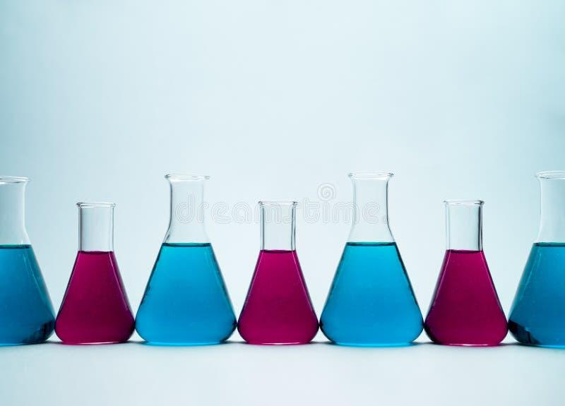 Erlenmeyer flasks. Multiple erlenmeyer flasks over light blue background stock photos