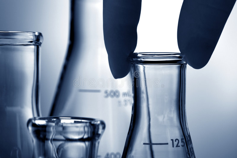 Erlenmeyer Flasks in Science Research Lab. Scientist hand holding a laboratory glass conical Erlenmeyer flask for an experiment in a science research lab stock photography