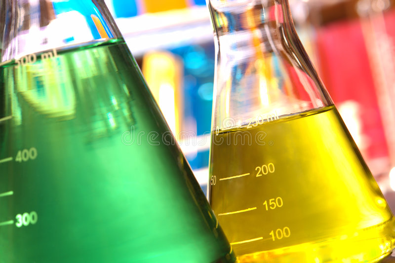 Erlenmeyer Flasks in Science Research Lab. Laboratory glass conical Erlenmeyer flasks filled with yellow and green chemical liquid for an experiment in a science royalty free stock photo