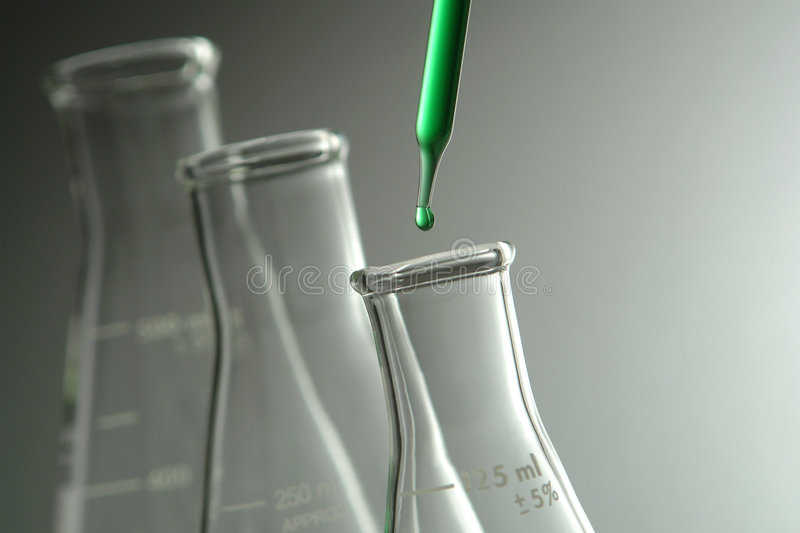 Erlenmeyer Flasks in Science Research Lab. Laboratory pipette with drop of green liquid over glass conical Erlenmeyer flasks for an experiment in a science royalty free stock photos