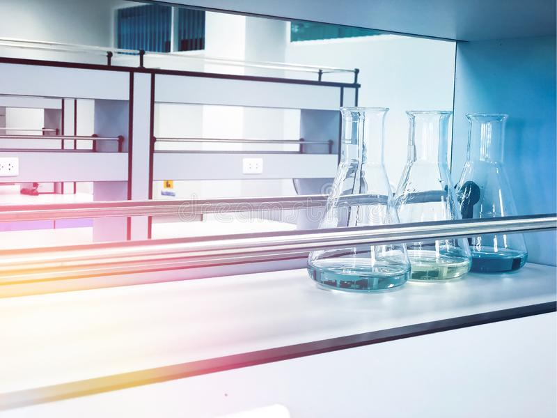 Erlenmeyer flasks on shelf in chemistry laboratory with blue solvent indicator, titration water sampleใ. Erlenmeyer flasks on shelf in chemistry laboratory stock images