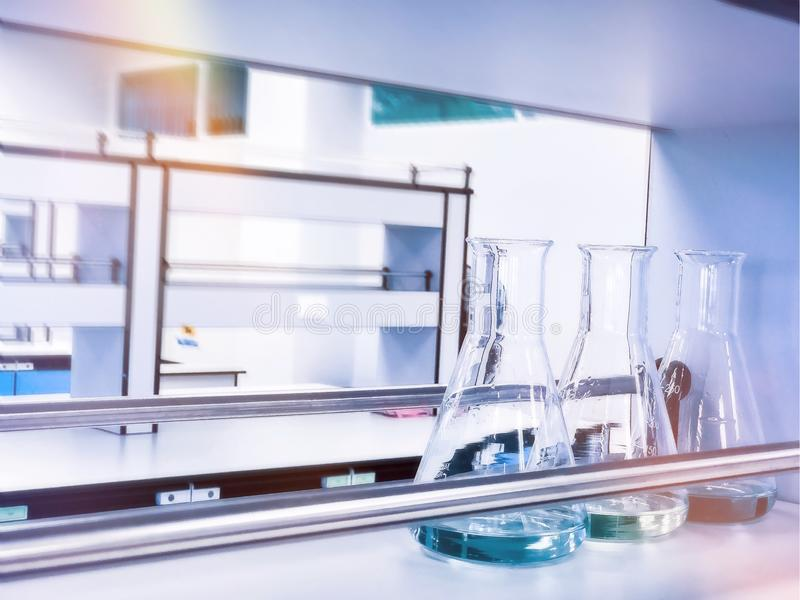 Erlenmeyer flasks on shelf in chemistry laboratory with blue solvent indicator, titration water sample stock photography