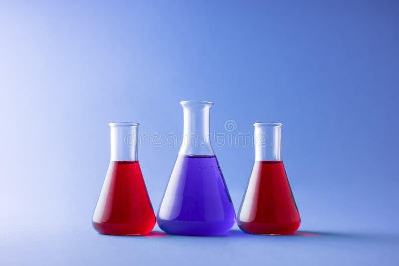 Erlenmeyer flasks. Three erlenmeyer flasks over colorful background stock photo