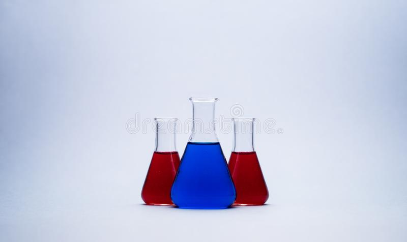 Erlenmeyer flasks. Three erlenmeyer flasks over colorful background royalty free stock photos