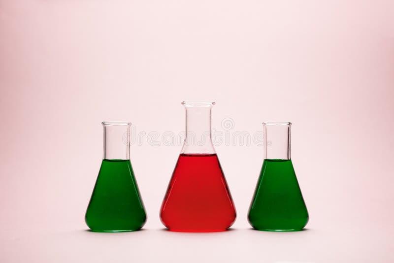 Erlenmeyer flasks. Three erlenmeyer flasks over light pink background stock photography