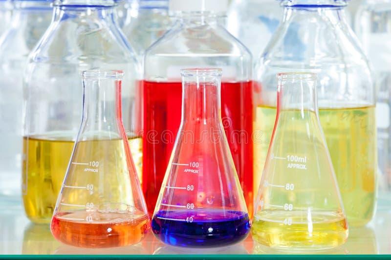 Erlenmeyer-flessen met chemische oplossingen stock afbeelding