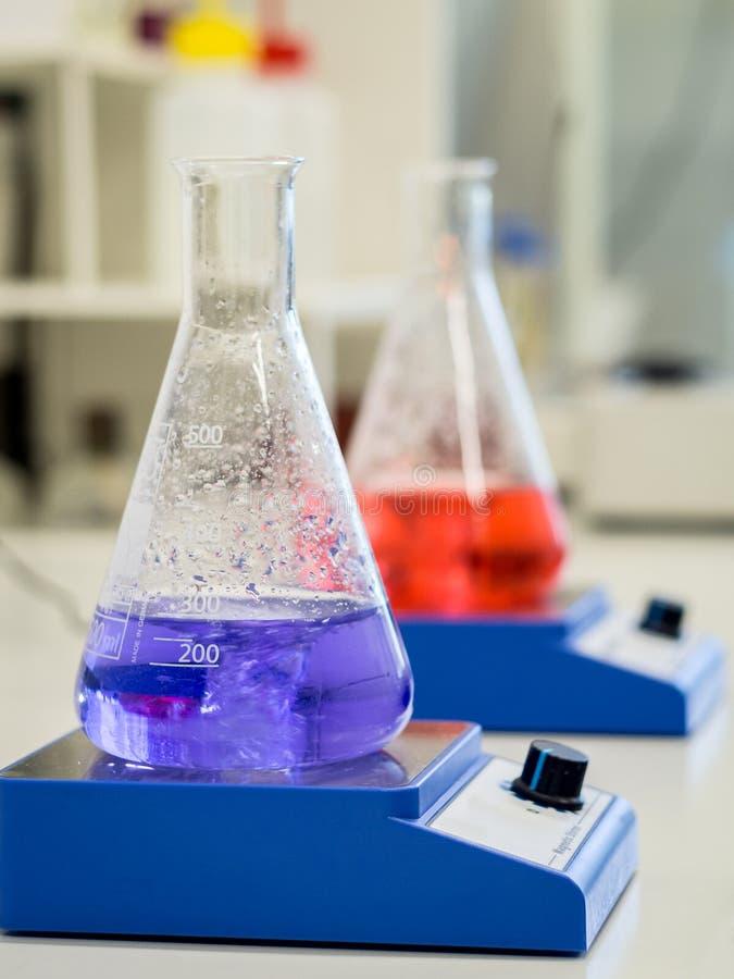 Erlenmeyer-flessen met kleurrijke oplossingen stock foto's