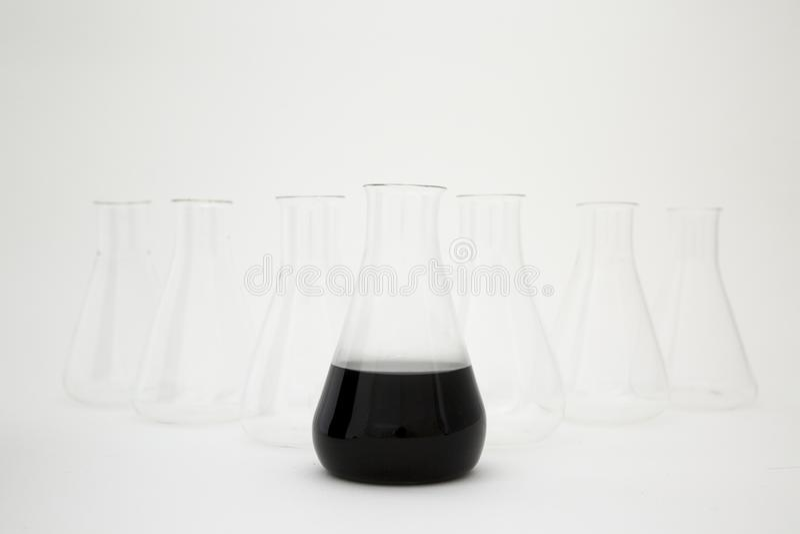 Erlenmeyerkolv av vetenskapligt laboratorium, fylld med svart vätska med glasfiberutrustning på vit bakgrund royaltyfri foto