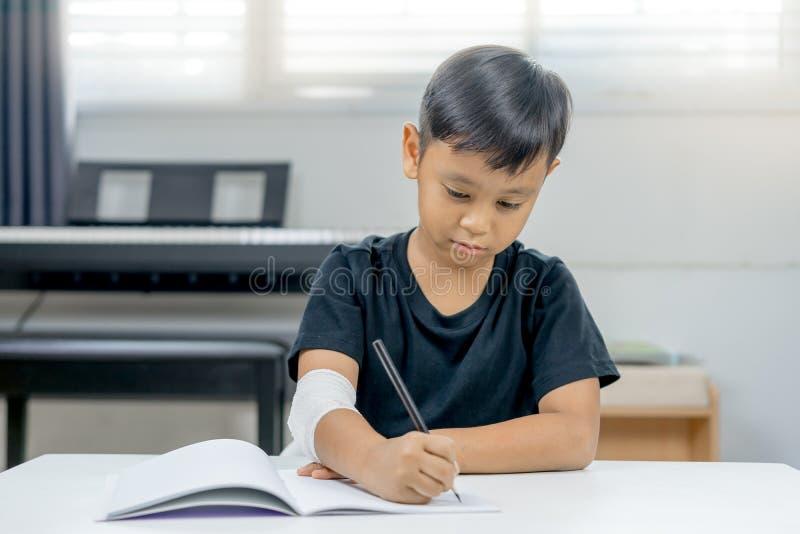 Ermüden asiatische Jungen an den verletzten Händen vom Schreiben eines Notizbuches stockbild
