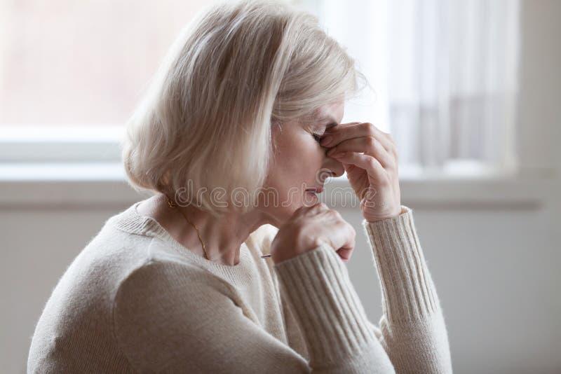 Ermüdete umgekippte ältere Frau, die Nasenbrückengefühls-Augenstr massiert stockfotografie