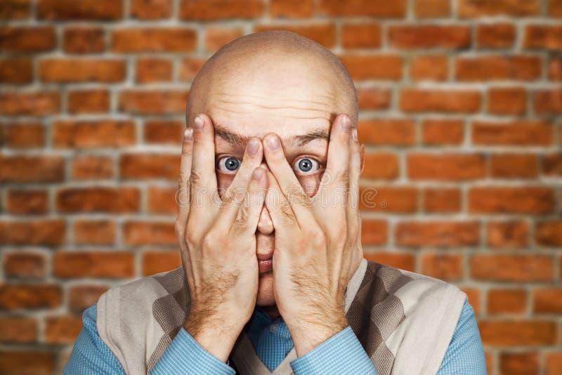 Ermüdung, Krisen-Konzept - Porträt-kahle Mann-Gleiche durch seine Finger auf Backsteinmauerhintergrund stockfotos