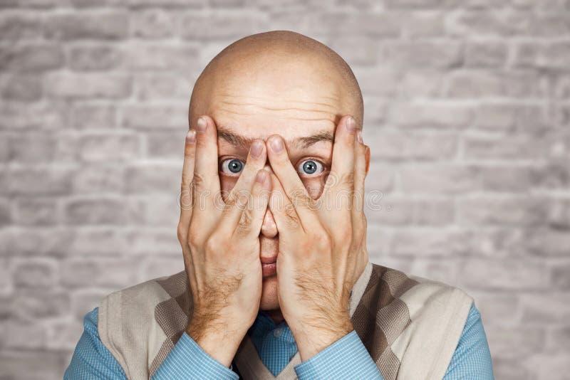 Ermüdung, Krisen-Konzept - Porträt-kahle Mann-Gleiche durch seine Finger auf weißem Hintergrund der Backsteinmauer lizenzfreies stockbild