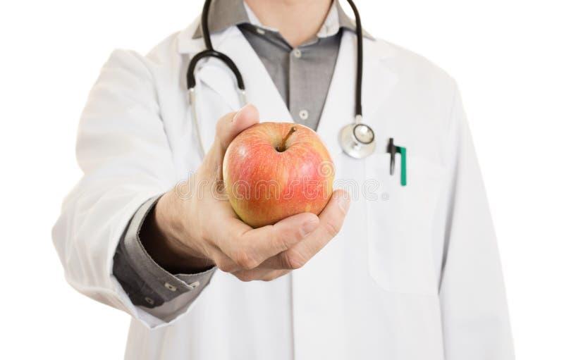 Ernährungswissenschaftlerdoktor, einen Apfel gebend, lokalisiert lizenzfreies stockfoto