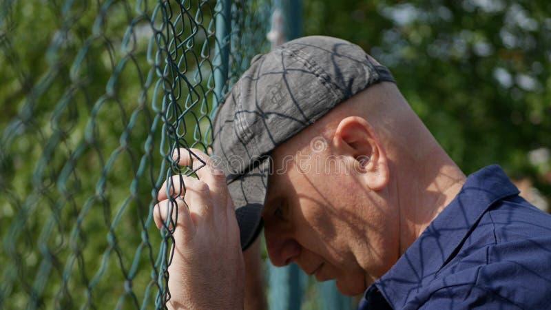 Ernüchterter und hoffnungsloser Mann, der mit den Händen auf metallischem Zaun hängt stockbilder