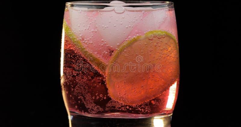 Erneuerndes rotes Getränkcocktail in einem Glas mit Eis und Kalk Sprudelndes Wasser des Sodas stockfotos