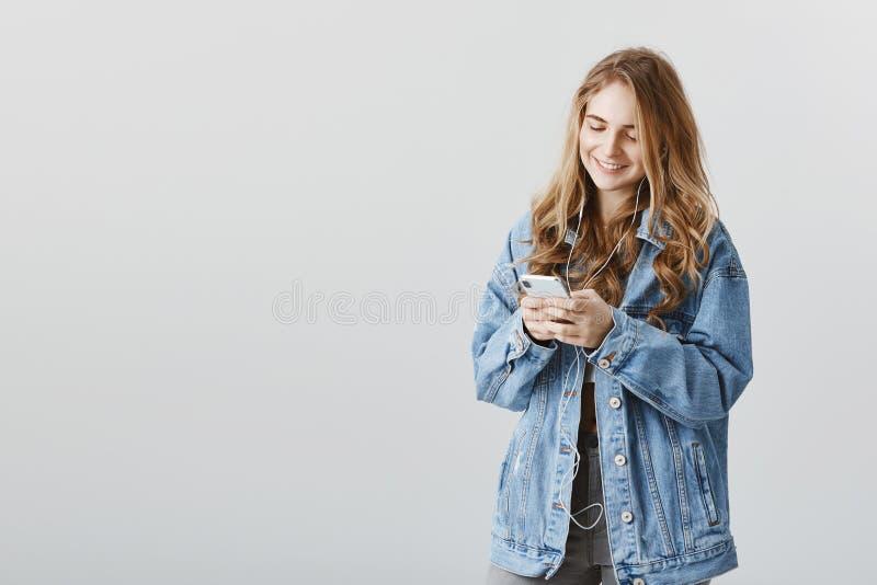 Erneuerte Titelliste mit neuen Liedern Porträt der erfüllten glücklichen attraktiven Frau in der Denimjacke, die Smartphone hält lizenzfreie stockfotografie
