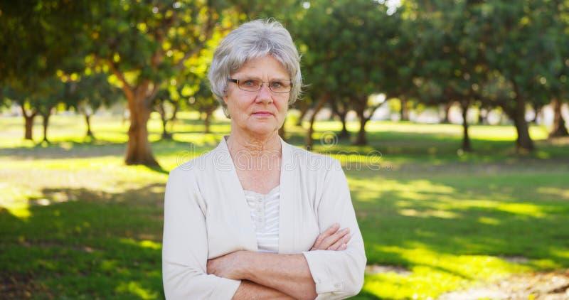 Ernste ältere Frau, die im Park steht stockbilder