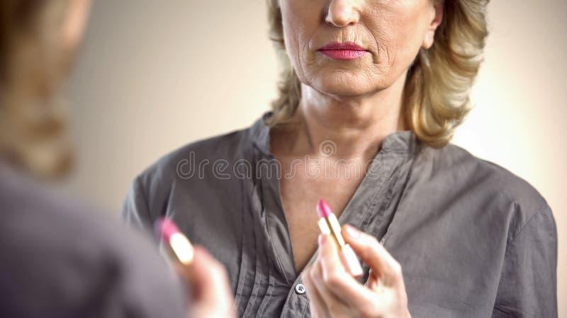 Ernste ältere Frau, die Lippenstift vor Spiegel, Geschäftstreffen anwendet stockfotos