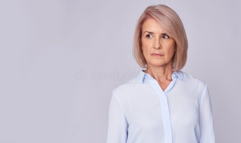 Ernste ältere Frau, die weg schaut stockbilder
