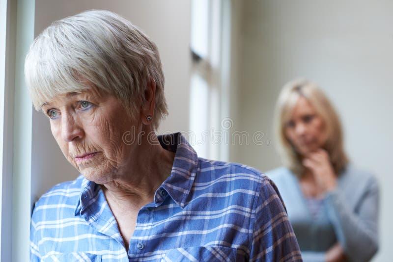 Ernste ältere Frau mit erwachsener Tochter zu Hause lizenzfreie stockbilder