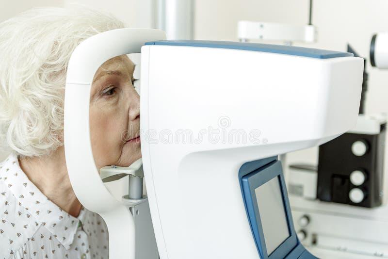 Ernste alte Frau, die nahe optischem Apparat sitzt lizenzfreies stockfoto