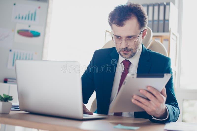 Ernste Arbeitskraft schreibt Informationen von Tablette zu Laptop Er i lizenzfreie stockfotos