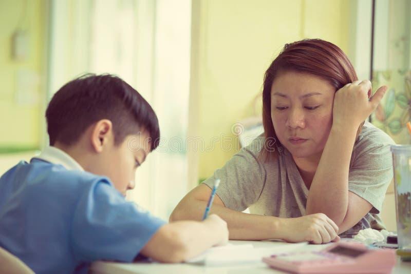Ernste asiatische Mutter-helfender Sohn mit Hausarbeit stockfotos
