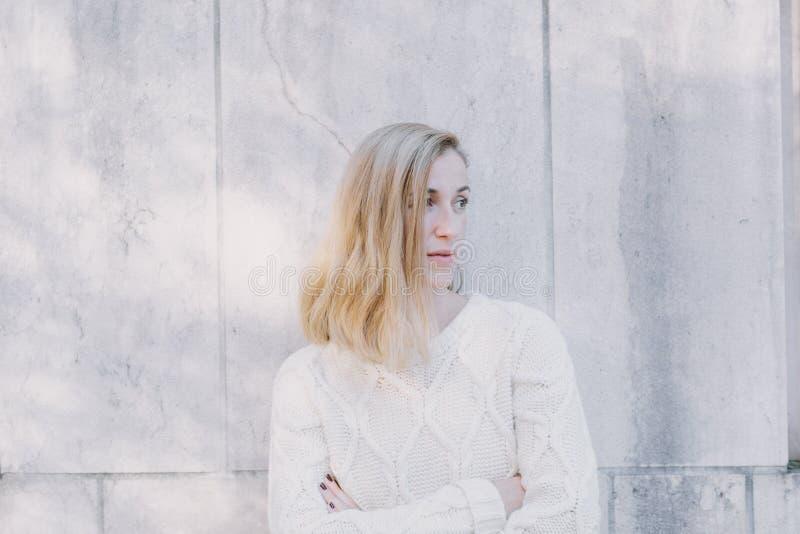 Ernste attraktive blonde Frau, die aufpassend steht stockfotos