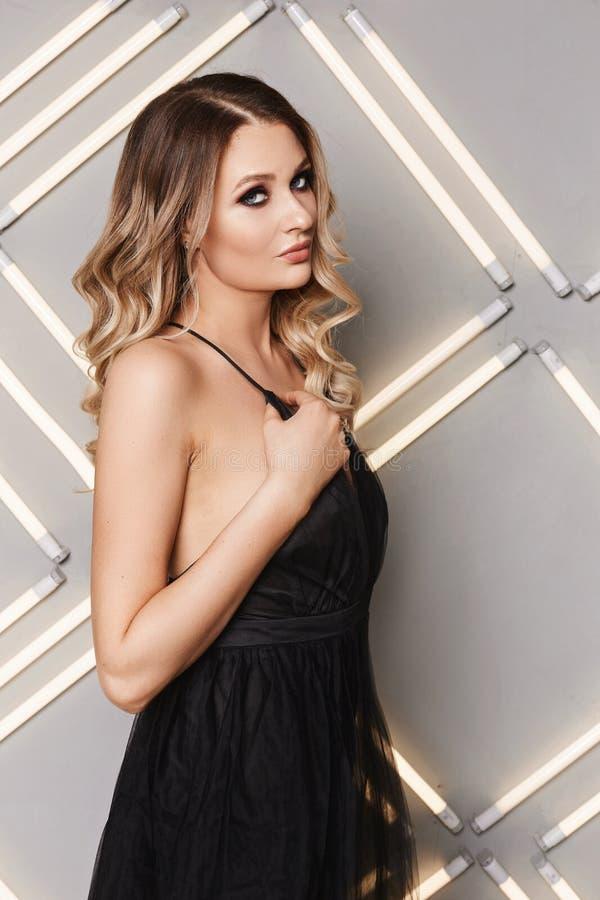 Ernste Blondine mit Frisur und Make-up im schwarzen Kleid lizenzfreie stockfotos