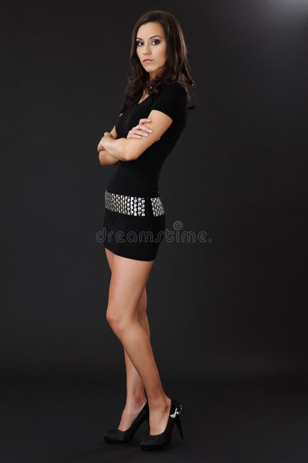 Ernste Brunettefrau, die auf dunklem Hintergrund aufwirft stockfoto