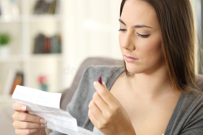 Ernste Frau, die eine Medizin liest eine Broschüre hält stockfoto