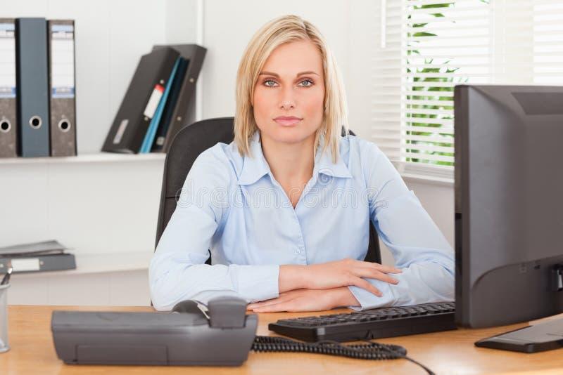 Ernste Frau, die hinter einem Schreibtisch sitzt lizenzfreie stockfotos