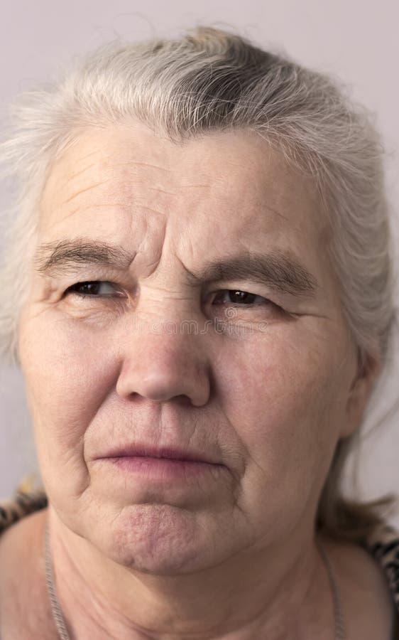 Ernste Frau mit dem grauen Haar auf ihrem Kopf stockbild