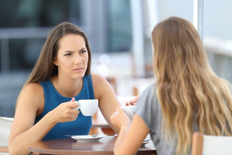 Ernste Freunde, die ein Gespräch in einer Stange haben stockbild